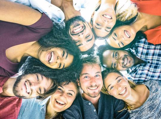 Blije mensen met verschillende huidskleur in een kring